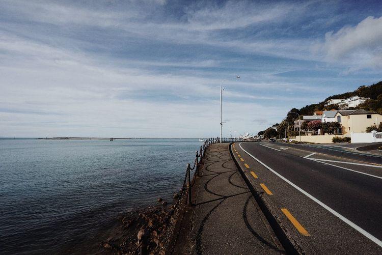Coastal road by sea against sky