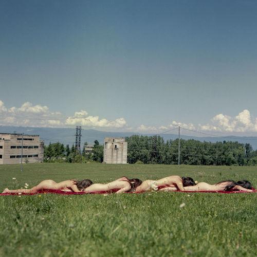Woman sleeping on grass against sky