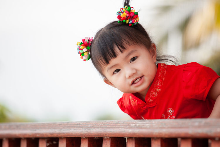 Happy cute asian little child girl in chinese tradition dress smiling and wishing you a happy in Chinese New Year Child Innocence One Person Kid Girl Asian  Adorable Cute Baby Toddler  Smile Chinese Japanese  Thai Innocence Happy Cheerful Playing Portrait Lovely Lifestyles Tradition Chinese New Year Celebration Wish