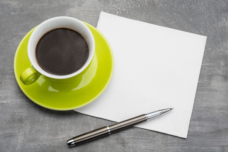 Green cup of coffee with clean napkin and a metal ballpoint pen on grey background Coffee Brainstorming Morning Drink Inspiration Table Grey Paper Mug Cup Contemplation Planning Pen Message Thoughts Ideas Blank Reminder Write Steam Start Note Steamy Napkin Copy Paste