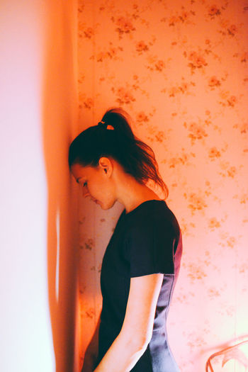 Colored Background Dark Hair Guilt Indoors  Intimacy Light And Shadow Loneliness One Person Only Women Ponytail Sadness Side View Standing Warm Light Young Women