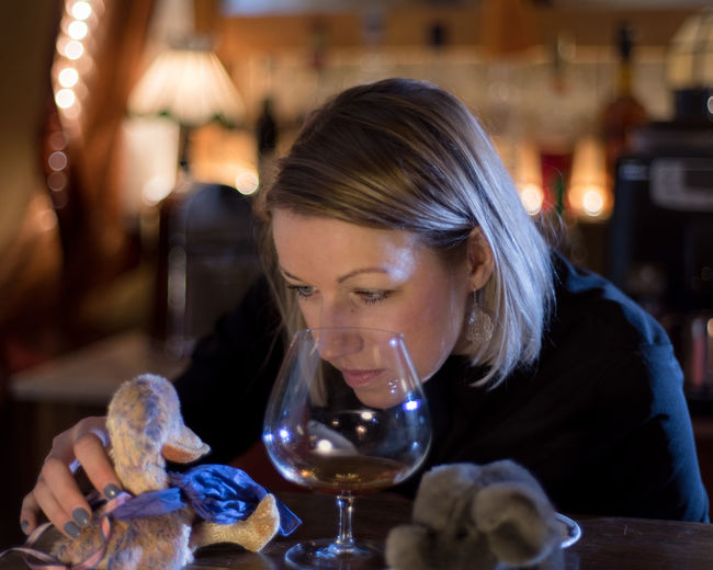 Close-up of mid adult woman holding toys by wineglass on restaurant table