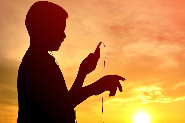 Silhouette Boy Listening Music Through Mobile Phone Against Cloudy Sky During Sunset