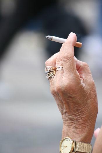 Senior Person Holding Cigarette In Hand