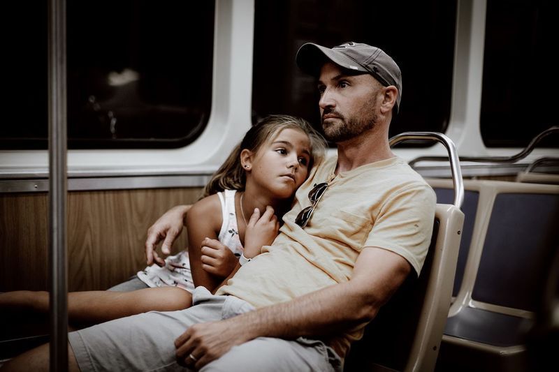 Man sitting with daughter in train