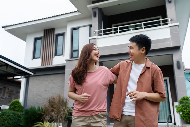 Young couple standing outside house in building