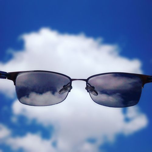 Low angle view of sunglasses against cloudy sky