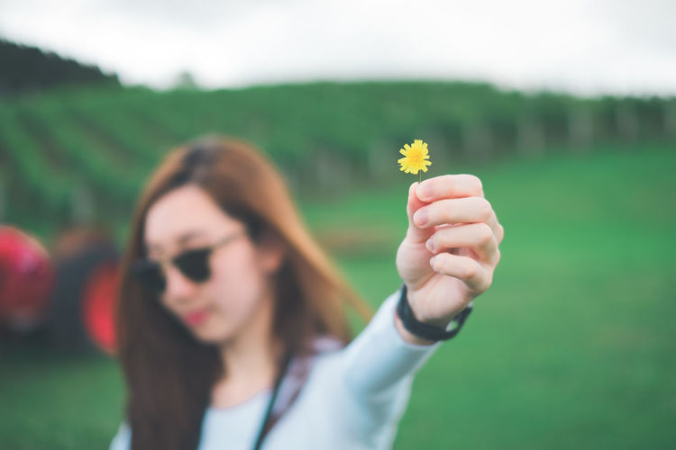 Young woman holding small yellow flower while standing on field