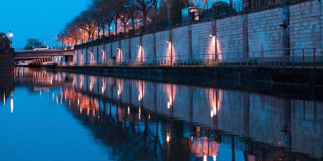 Bridge over canal against blue sky