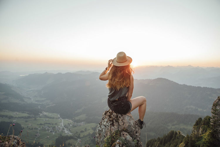 Full length of young woman against mountains during sunset