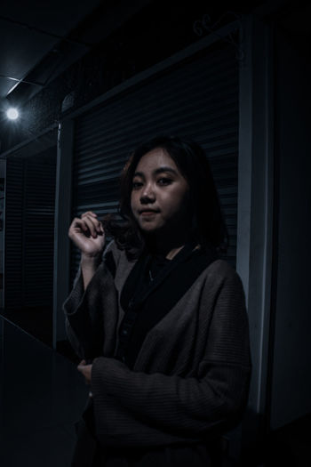 Portrait of young woman in dark