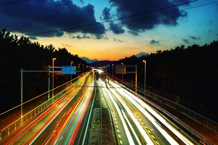 Light Trails On Road In City Against Sky During Sunset