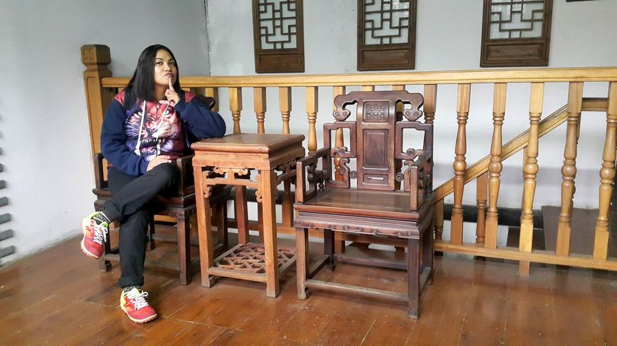 Full Length Of Woman Sitting On Chair At Home