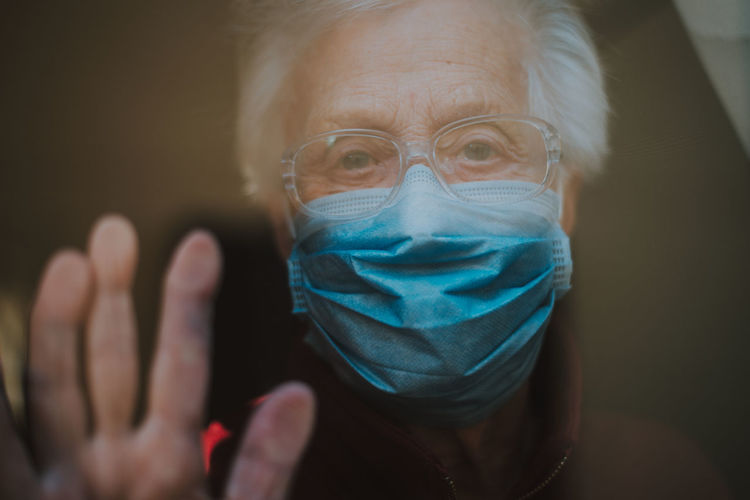 Close-up portrait of senior woman wearing mask looking through window