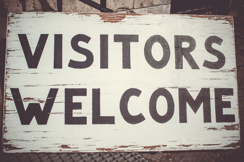 Visitors welcome Text Western Script Communication Capital Letter Sign Information No People Information Sign Close-up Day Outdoors Message Advertisement Warning Sign Black Color Hanging Wall - Building Feature White Color Wall Road Sign