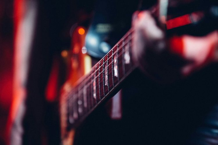 Midsection of person playing guitar on stage