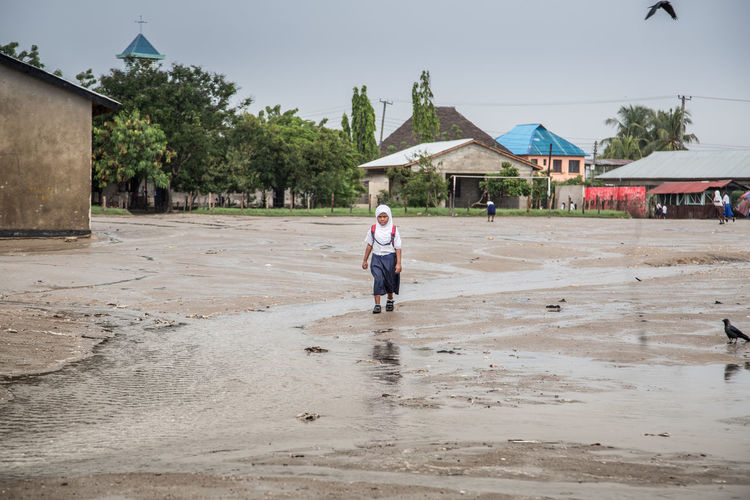 Full length of cute girl walking on wet land against sky