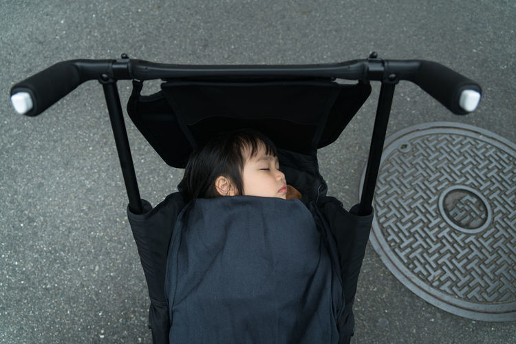 High Angle View Of Girl Sleeping In Stroller On Road