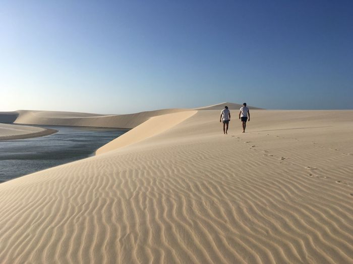 Men walking on sand dune in desert against blue sky