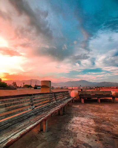 Empty benches at san gabriel valley airport against cloudy sky during sunset