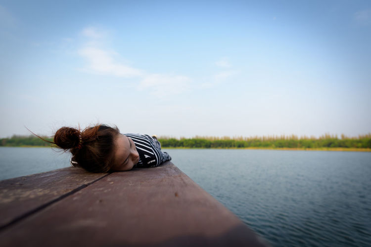 Woman Lying On Pier Over Lake Against Sky