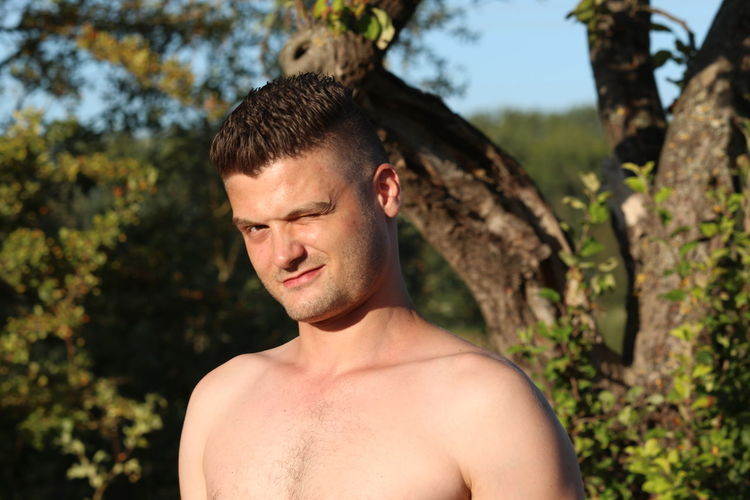 Portrait of shirtless man winking eye against trees in forest