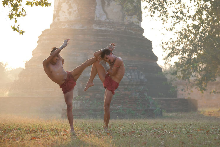 Shirtless men fighting against old temple at sunset