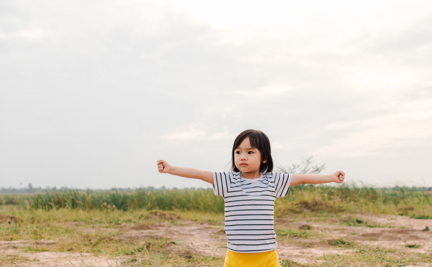 Girl With Arms Outstretched Standing On Field