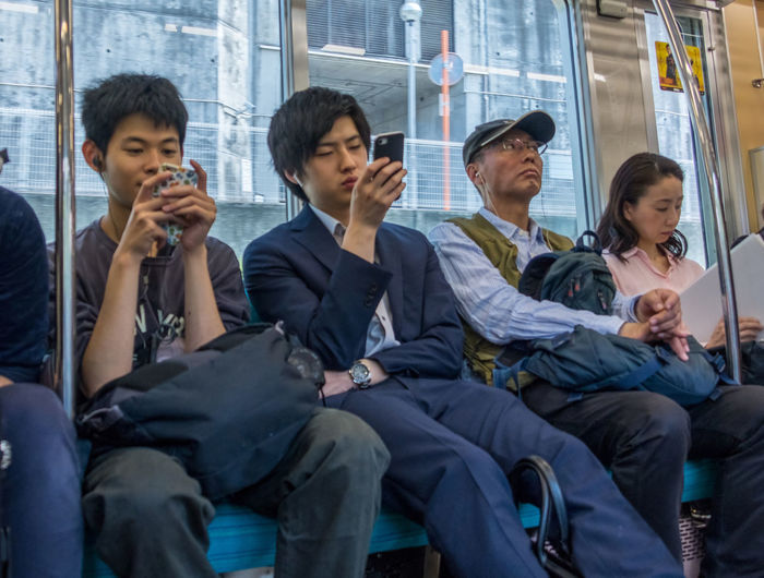 Group of people sitting on mobile phone
