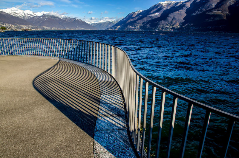 Walkway wit Railing and Shadow on Alpine Lake Maggiore with Mountain in Ticino, Switzerland. Railing Shadow And Light Beauty In Nature Day Lake Lake Maggiore Mountain Mountain Range Nature No People Outdoors Railing Scenics Sea Shadow Sky Street Sunlight Swiss Alps Tranquil Scene Tranquility Walkway Water Waterfront
