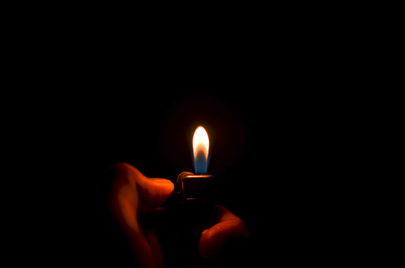 Cropped Image Of Hand Igniting Lighter Against Black Background