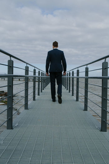 Rear view of businessman walking on pier over sea against sky