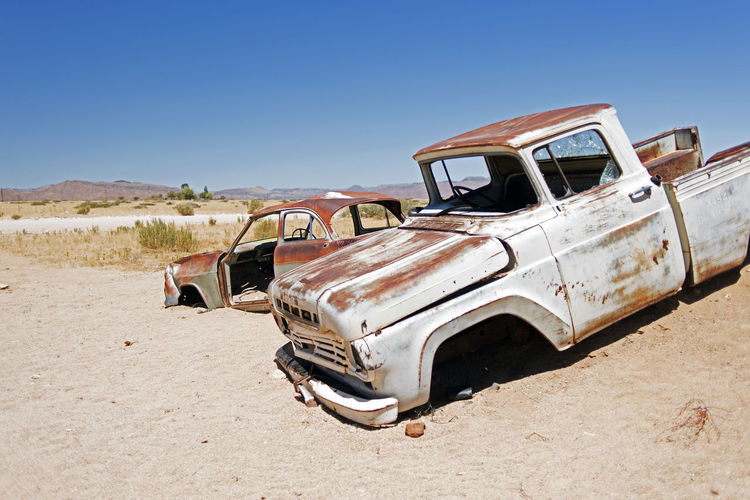 Wrecked and junk cars in the desert Land Mode Of Transportation Transportation Abandoned Sky Sunlight Land Vehicle Clear Sky Car Day Nature Field Old Landscape Motor Vehicle Obsolete Damaged Rusty Environment Run-down Deterioration No People Outdoors Ruined Wrecked Junk Africa Desert Travel