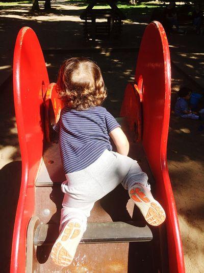 Rear View Of Boy Climbing Slide