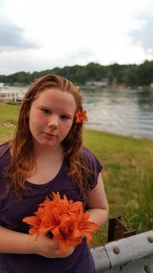 Portrait of teenage girl with orange lilies against lake