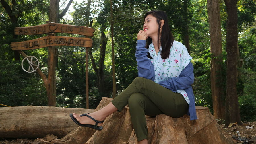 Beautiful young woman sitting on seat against trees