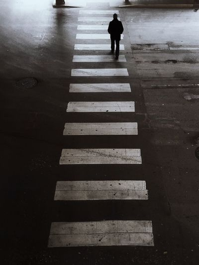 Rear View Of Man Walking On Zebra Crossing