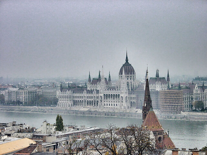 Hungarian parliament building by danube river against sky in city