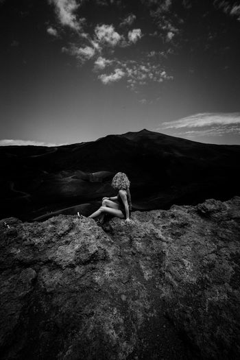 Side view of mid adult woman sitting on mountain against sky