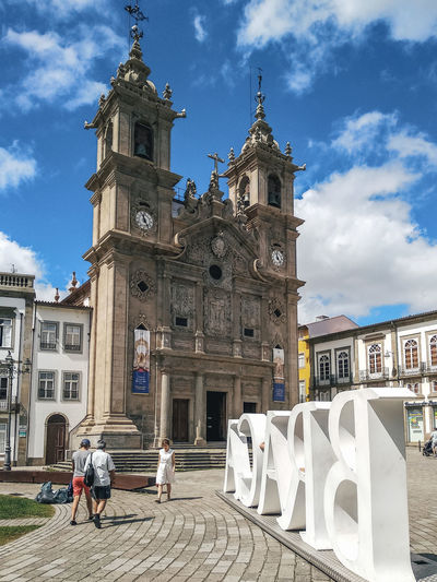 Group of people in front of church building against sky in braga, portugal