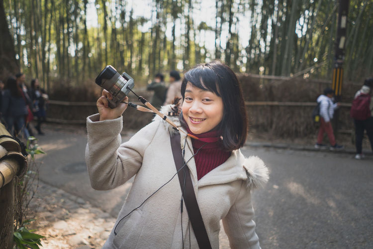 Portrait of smiling young woman holding camera while standing against trees