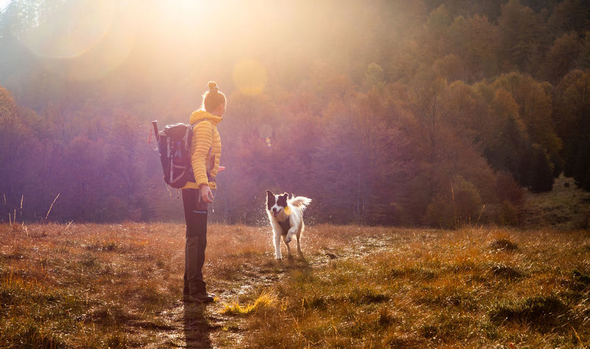 Full length of woman standing with dog on field
