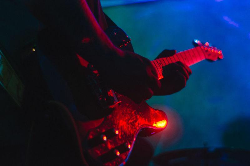 Midsection Of Man Playing Illuminated Guitar At Night