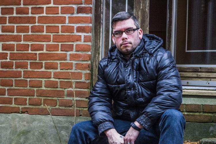 Man sitting against brick wall