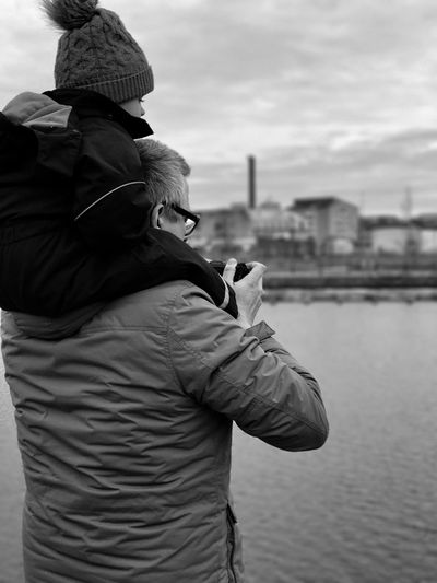 Rear view of father carrying daughter while standing by river against cloudy sky