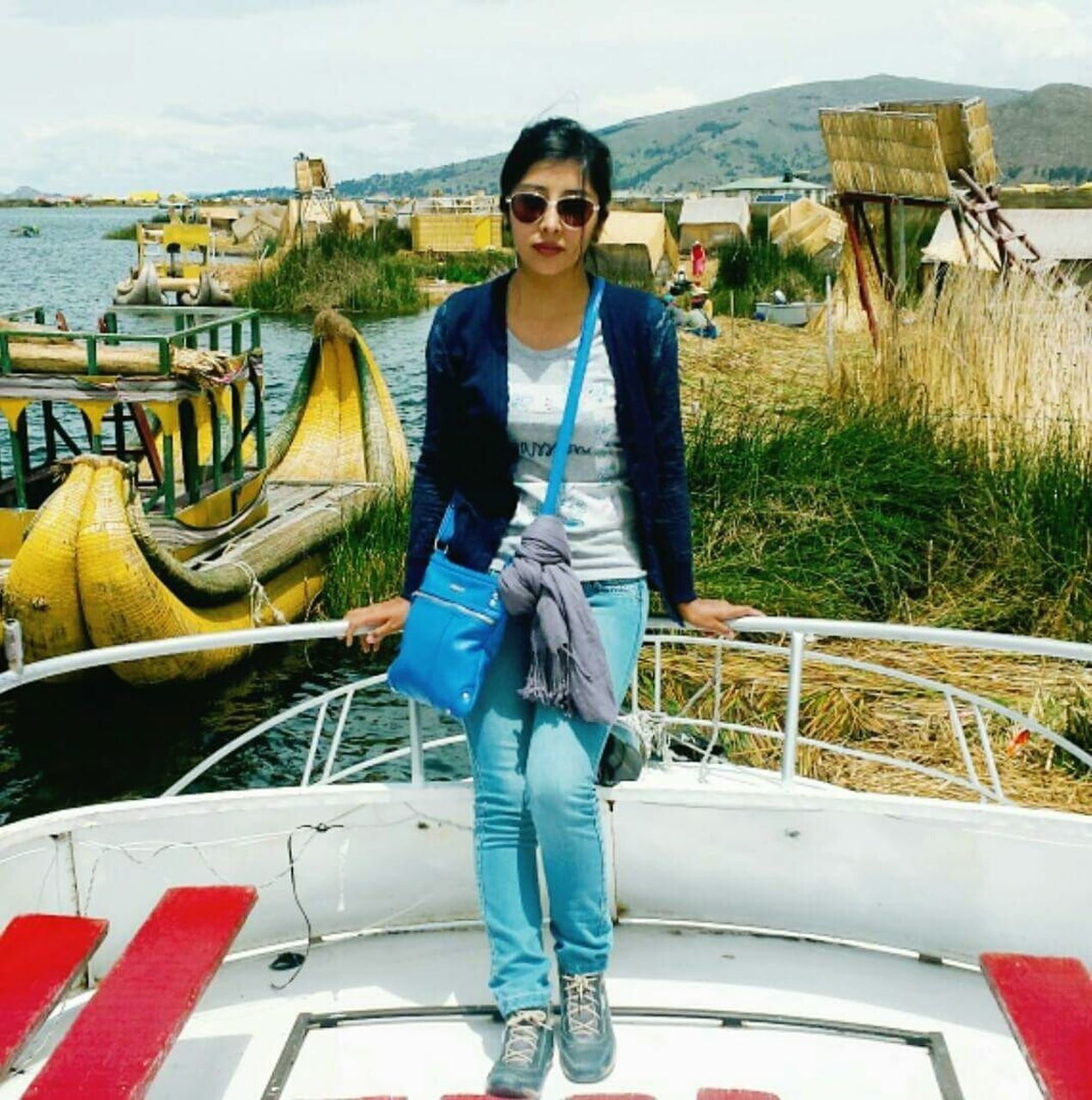 one person, young adult, front view, sunglasses, standing, looking at camera, real people, portrait, casual clothing, young women, day, outdoors, leisure activity, full length, smiling, one young woman only, lifestyles, beautiful woman, nautical vessel, adults only, adult, people