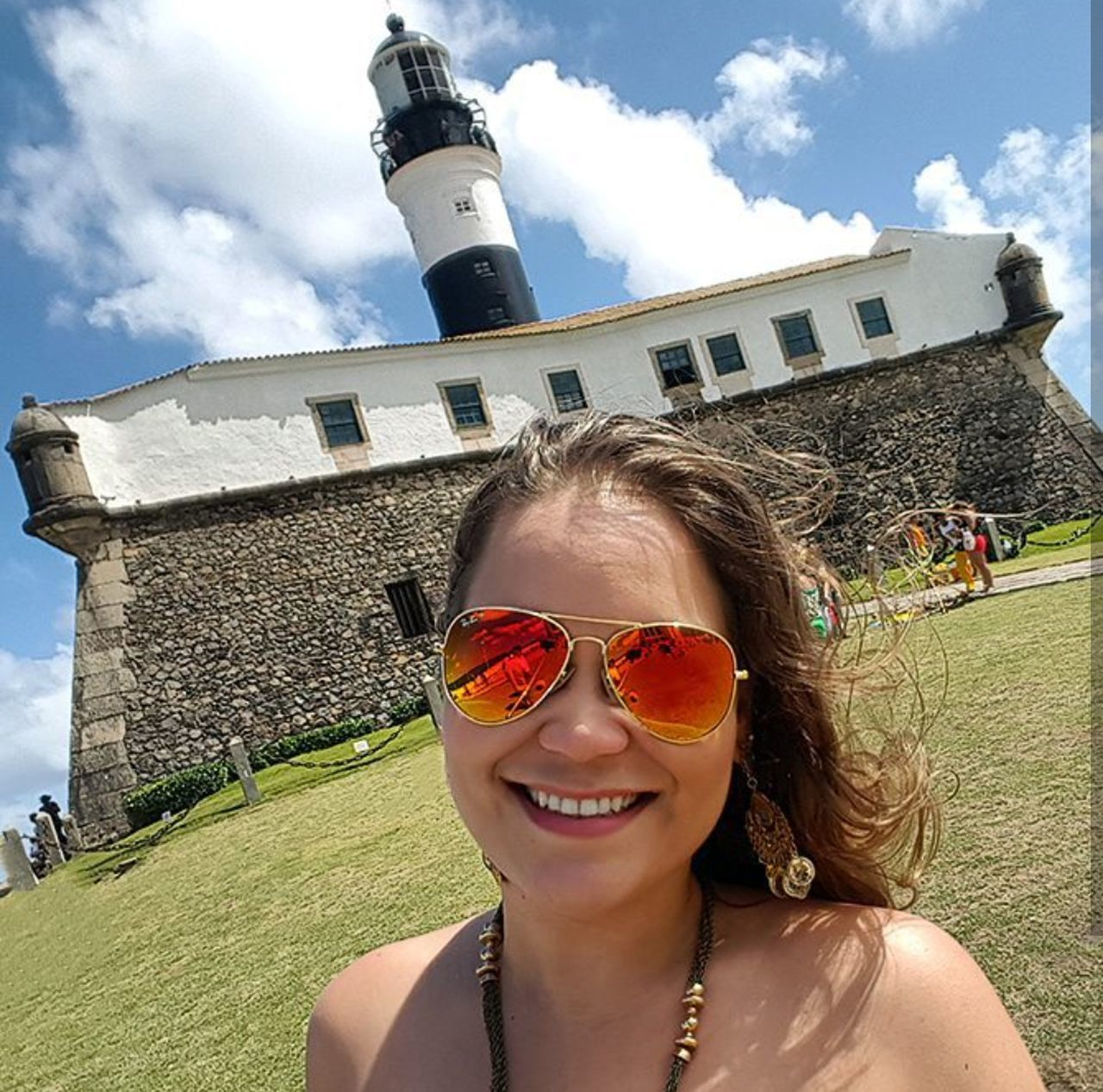 sunglasses, architecture, sky, building exterior, smiling, built structure, looking at camera, portrait, cloud - sky, outdoors, real people, leisure activity, day, happiness, vacations, one person, cheerful, sunlight, travel destinations, young adult, grass, lifestyles, young women, nature, adult, people