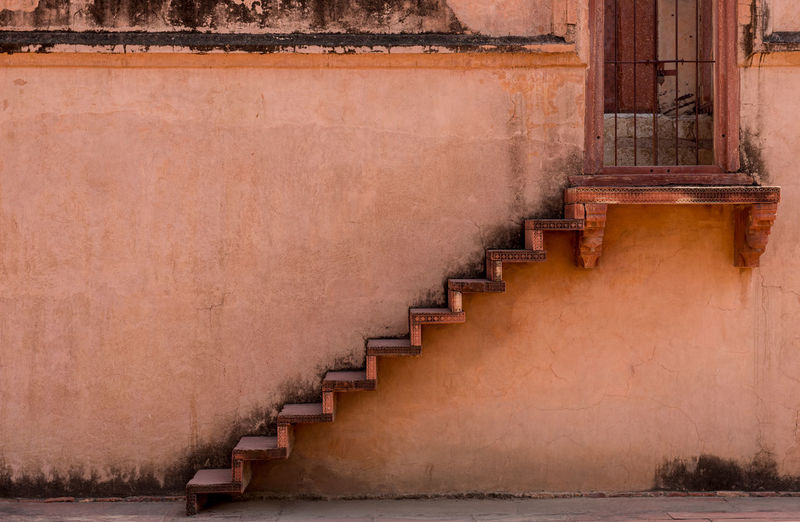 Traditional staircase leading to a metal closed door outside an orange wall of an indian house