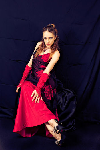 Red and Deep Purple Deep Purple Dress Elégance Stylish Beautiful People Beautiful Woman Beauty Dress Elegance And Class Fashion Fashion Model Female Full Length Glamour Lifestyles Looking At Camera Make-up Model Portrait Purple Red Sitting Studio Shot