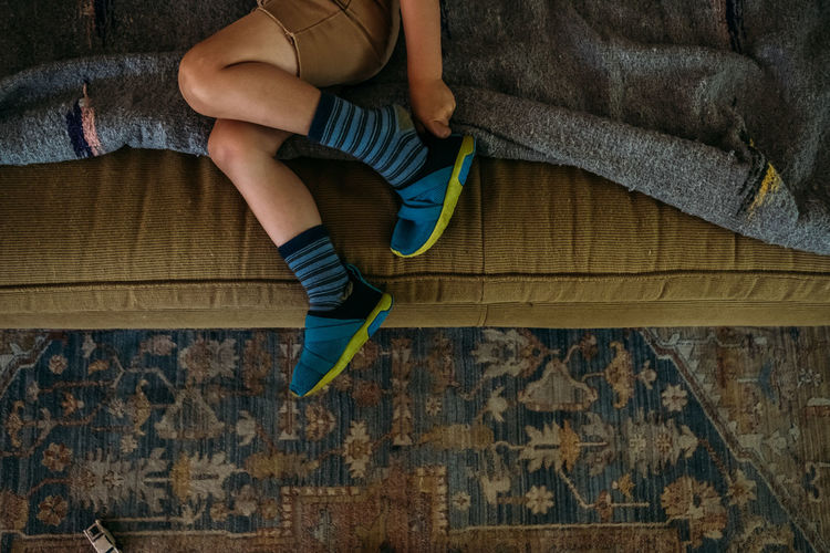 Low section of boy sitting on sofa at home